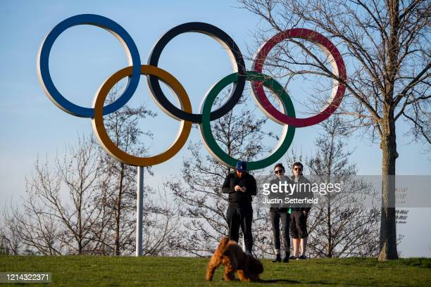 People walk there dog under the Olympic rings in the Olympic Park in Stratford as Tokyo Olympics organisers are considering options to delay the...