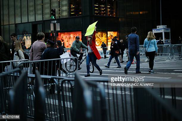 People walk through 5th Avenue near Trump Tower after the street was closed to foot traffic by police with barricades and officers at the entrance to...