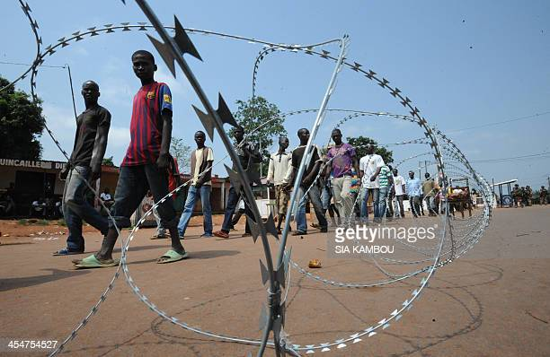 People walk through a checkpoint held by French soldiers of the Sangaris operation on December 10 2013 in the North of Bangui Two French soldiers...