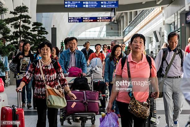 People walk through a concourse with their luggage at Hong Kong International Airport in Hong Kong China on Monday June 15 2015 The Hong Kong...