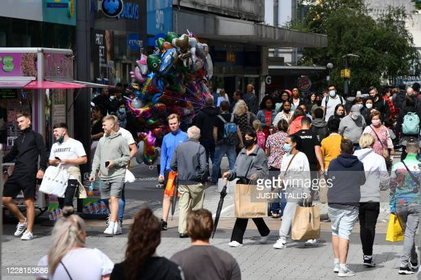 People walk through a crowded shopping street in Birmingham, central England on August 22 as Britain's second-city, home to more than one million...