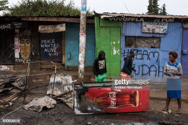 People walk through a damaged area of the Kibera slum on August 12 2017 in Nairobi Kenya Police clashed with opposition supporters overnight as Uhuru...