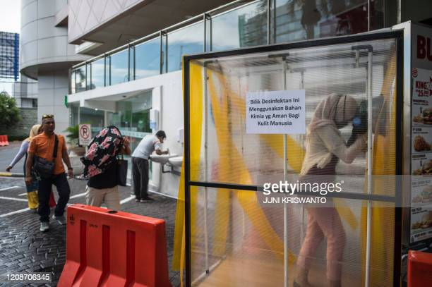 TOPSHOT People walk through a disinfectant chamber as a preventive measure against the COVID19 coronavirus before entering a shopping mall in...