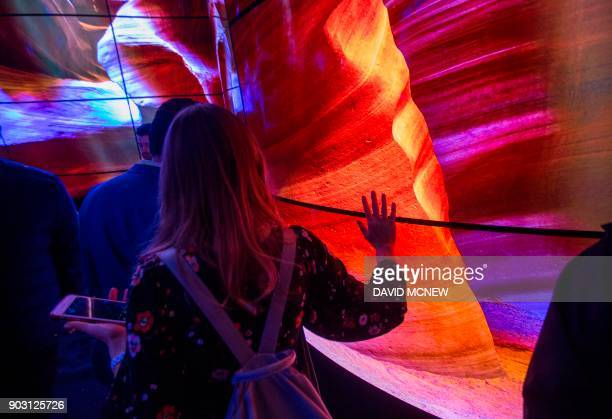 People walk through a display of LG OLED televisions at CES in Las Vegas Nevada January 9 2018 / AFP PHOTO / DAVID MCNEW