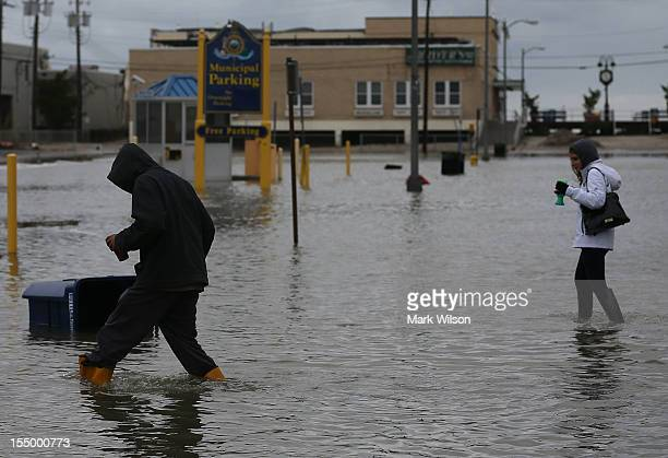 People walk through a flooded street, on October 30, 2012 in Ocean City, New Jersey. Hurricane Sandy made landfall last night on the New Jersey...