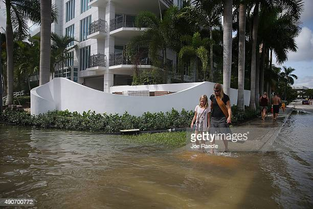 People walk through a flooded street that was caused by the combination of the lunar orbit which caused seasonal high tides and what many believe is...
