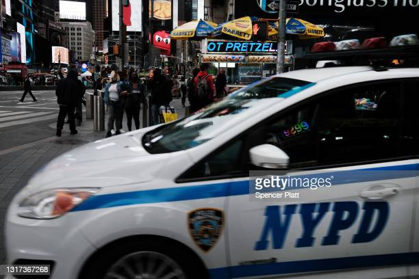 People walk through a heavily policed Times Square on May 10, 2021 in New York City. Three bystanders, including a 4-year-old girl, were injured...