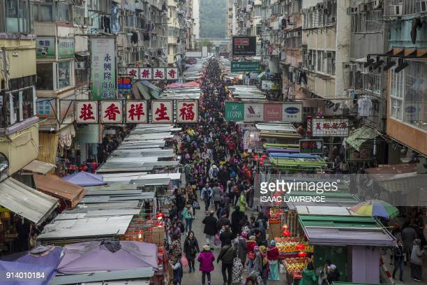 TOPSHOT People walk through a market crowded with shoppers in the Kowloon district of Hong Kong on February 4 ahead of the coming Lunar New Year The...