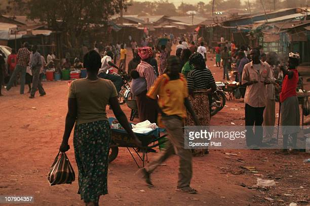 People walk through a market in the southern Sudanese city of Juba January 6 2011 in Juba Sudan One of the world's poorest countries Sudan is...