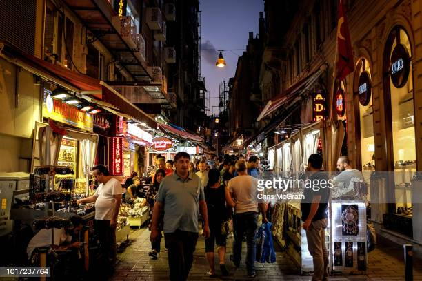 People walk through a market street on August 15 2018 in Istanbul Turkey The Turkish Lira recovered to trade at 61 USD despite President Erdogan...