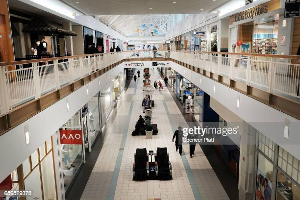 People walk through a nearly empty shopping mall on March 28 2017 in Waterbury Connecticut As consumers buying habits change and more people prefer...