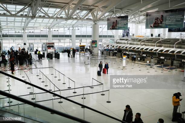 People walk through a nearly empty terminal at John F Kennedy Airport on January 31 2020 in New York City As fears grow around the globe over the...