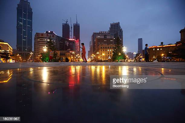 People walk through a park as buildings stand in the background at night in Dalian China on Tuesday Sept 10 2013 Goldman Sachs Group Inc last week...