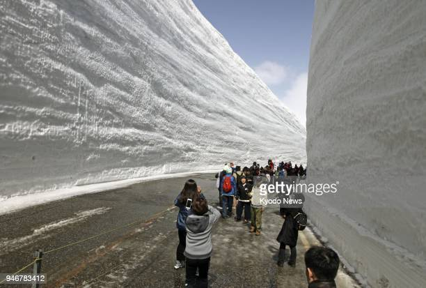 People walk through a pathway with snow walls as tall as 17 meters each side of the road in Toyama Prefecture on April 16 2018 The Tateyama Kurobe...