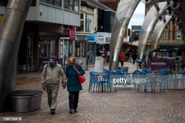 People walk through a quiet shopping street in the town centre on October 17, 2020 in Blackpool, England. Lancashire has entered tier 3 of the...