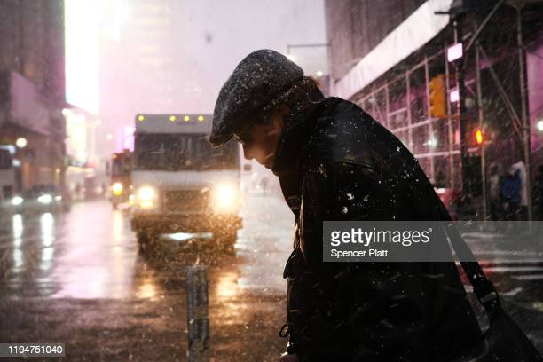 People walk through a snow squall in midtown Manhattan on December 18 2019 in New York City As the afternoon storm blew through the city with little...