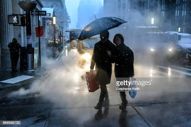 People walk through a snowy lower Manhattan on December 9 2017 in New York City The area is expected to see 36 inches of snow in the first snowfall...