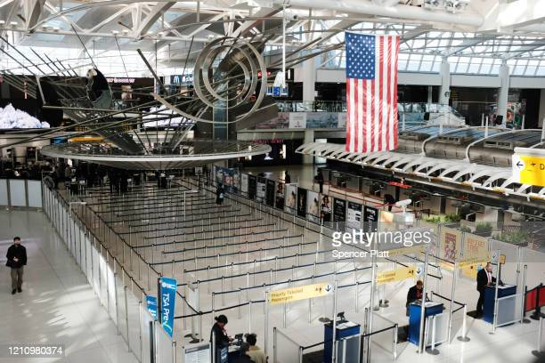 People walk through a sparse international departure terminal at John F Kennedy Airport as concern over the coronavirus grows on March 7 2020 in New...