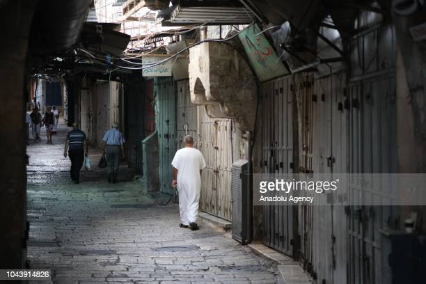 People walk through a street as shops closed in a general strike to protest against Israeli decision to demolish Khan alAhmar region in Eastern...