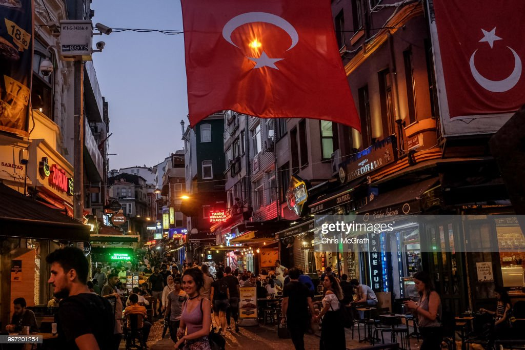 People walk through a street full of restaurants and bars on July 12, 2018 in Istanbul Turkey. Following Turkey's President Recep Tayyip Erdogan's re-election victory and the appointment of his son-in-law Berat Albayrak to lead the Treasury and Finance Ministry fears are growing that Turkey's economy is heading into crisis . The Turkish Lira, has plunged by approximately one-fifth this year raising prices for businesses and households.