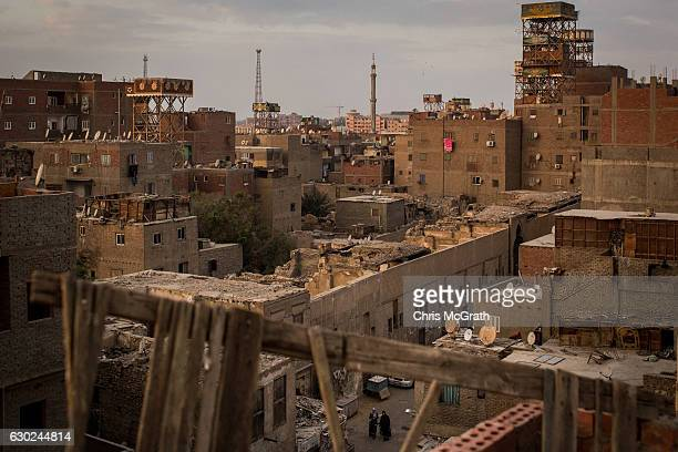 People walk through a street in the poor neighbourhood of the 'City of the Dead' on December 14 2016 in Cairo Egypt The 'City of the Dead' houses...