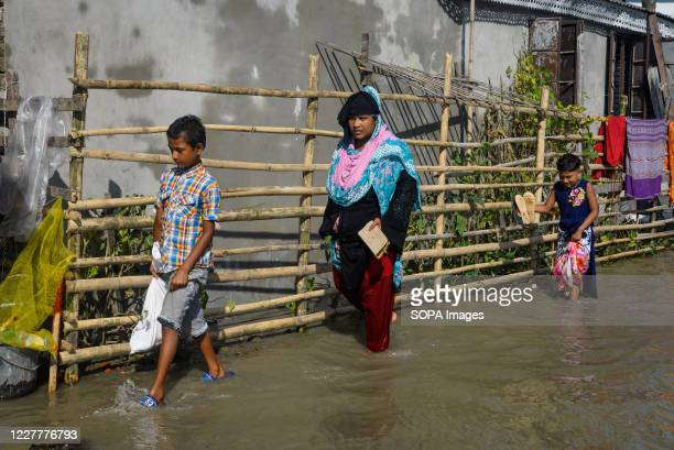 People walk through a submerged road. The flood situation is worsening in Munshiganj. Due to the heavy rain, the water level of the Padma River has...
