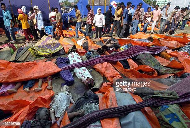 People walk through a temporary morgue in Banda Aceh 27 December 2004 as they try and find missing family members after a devastating quake and...