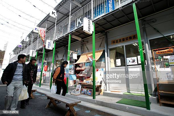 People walk through a temporary shopping area for displaced stores and restaurants in an area damaged by the tsunami following the Great East Japan...