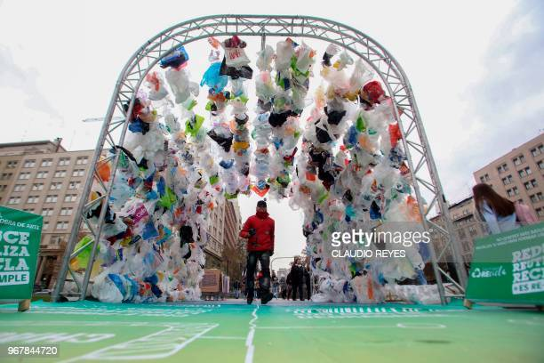 People walk through a tunnel made out of plastic bags in front of La Moneda presidential palace in Santiago during the World Environment Day on June...