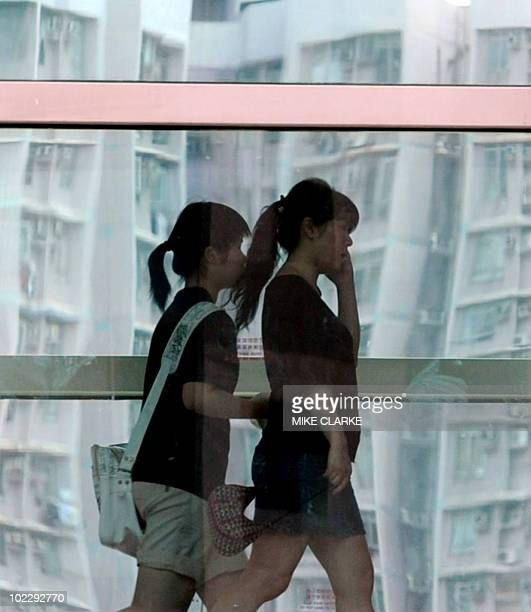 People walk through an air conditioned shopping mall past residential housing in Hong Kong on June 18 2010 As Hong Kong steams into summer millions...