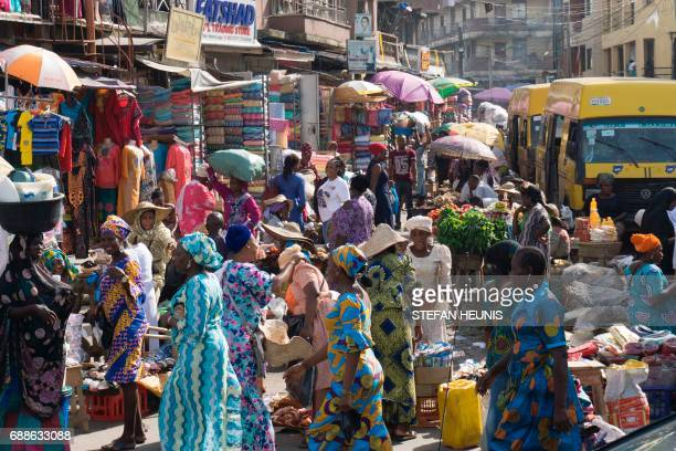 People walk through Balogun market in streets around Lagos Island on May 5 2017 Lagos is the world's 10th largest city with between 17 and 22 million...