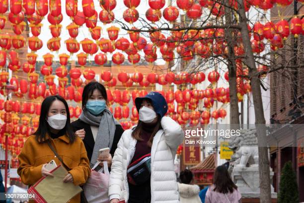 People walk through Chinatown on February 12, 2021 in London, England. This year's festivities, which usher in the Year of the Ox, take place whilst...