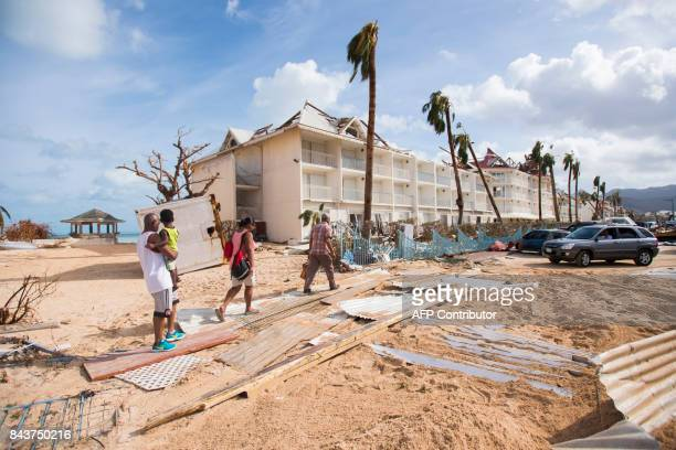 People walk through damage on September 7 in a sandcovered street of Marigot near the Bay of Nettle on the island of SaintMartin in the northeast...