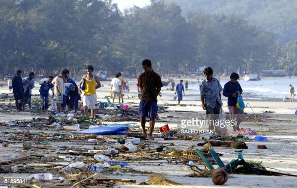 People walk through debris along the shoreline of Pathong beach of Phuket island southern Thailand 27 December 2004 a day after a tidal wave...