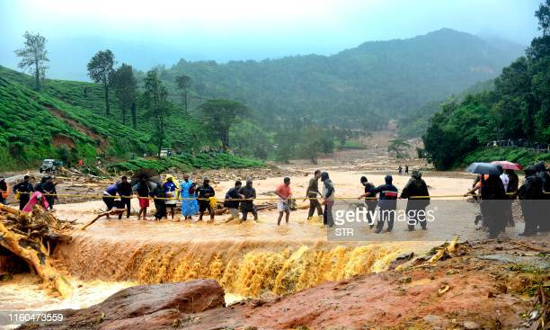 People walk through flood waters after a landslide in Meppadi Wayanad district in the Indian state of Kerala on August 9 2019 Floods that have killed...