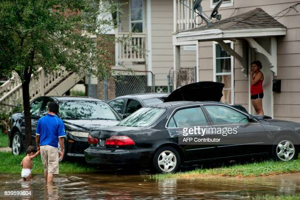 People walk through flooded streets as the effects of Hurricane Harvey are seen August 26 2017 in Galveston Texas Hurricane Harvey left a trail of...