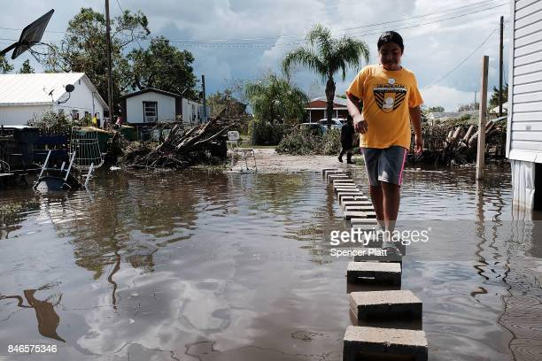 People walk through flooded streets in the rural migrant worker town of Immokalee which was especially hard hit by Hurricane Irma on September 13...