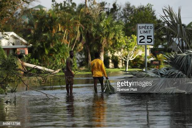 People walk through flooded streets the morning after Hurricane Irma swept through the area on September 11, 2017 in Fort Myers, Florida. Hurricane...