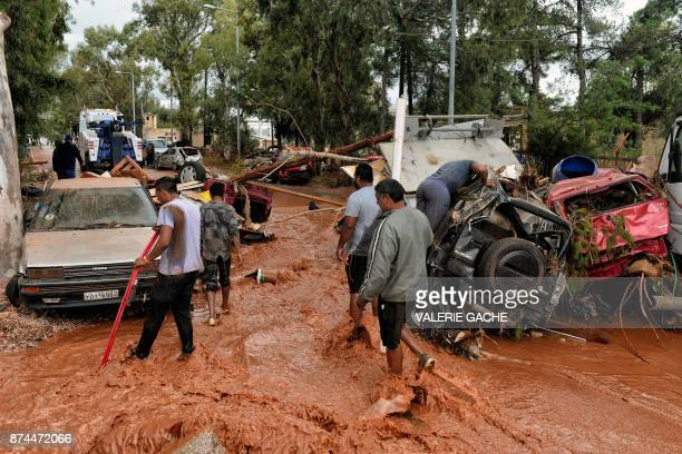 People walk through floodwater past damaged cars in the town of Mandra northwest of Athens on November 15 after heavy overnight rainfall in the area...