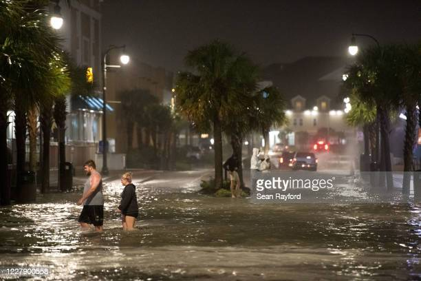 People walk through floodwaters on Ocean Blvd. August 3, 2020 in Myrtle Beach, South Carolina. Hurricane Isaias continued to move north along the...