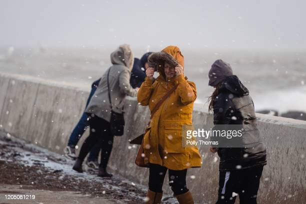 People walk through flying sea foam spray on February 09, 2020 in Porthcawl, United Kingdom. Amber weather warnings are in place as gusts of up to...