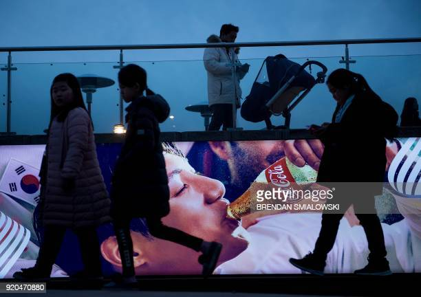 People walk through Gangneung Olympic Park during the Pyeongchang 2018 Winter Olympic Games in Gangneung South Korea on February 19 2018 / AFP PHOTO...