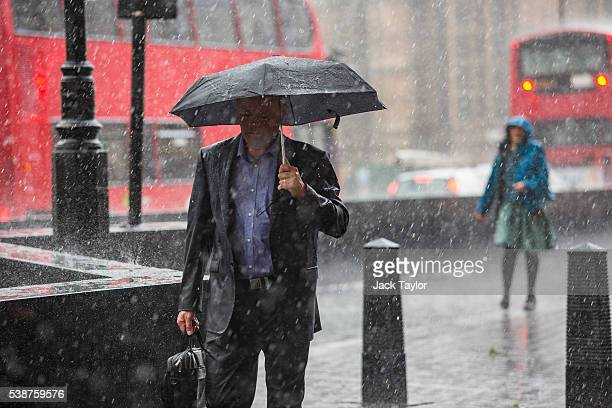 People walk through heavy rain in Westminster on June 8 2016 in London England The Met Office has issued flood alerts for parts of the south east of...