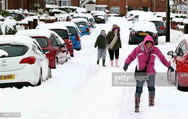 People walk through heavy snow covering the ground in Glengormley Northern Ireland on March 23 2013 Britain continued to be blitzed by unseasonal...