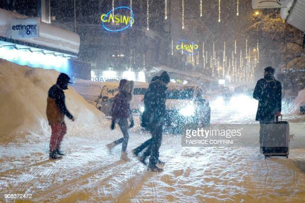 People walk through heavy snow fall in the resort town of Davos ahead of the World Economic Forum 2018 annual meeting on January 21 2018 in Davos...