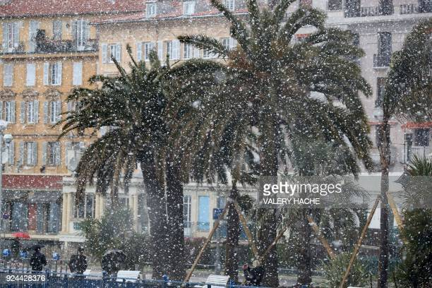 People walk through heavy snowfall along the Promenade des Anglais on February 26 2018 in Nice A wave of Siberian cold settled February 26 on the...