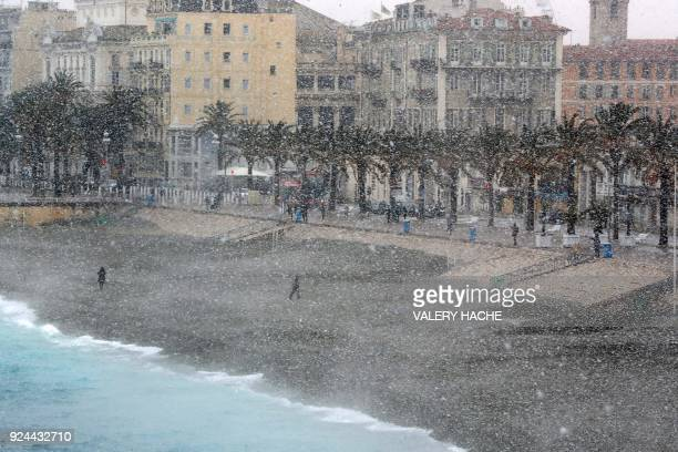 TOPSHOT People walk through heavy snowfall along the Promenade des Anglais on February 26 2018 in Nice A wave of Siberian cold settled February 26 on...