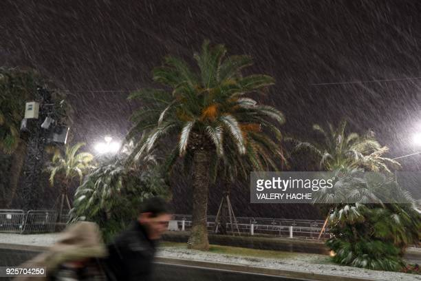 People walk through heavy snowfall along the Promenade des Anglais on February 28 2018 in Nice / AFP PHOTO / VALERY HACHE