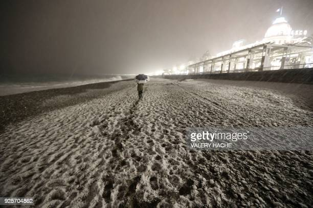 TOPSHOT People walk through heavy snowfall on the beach along the Promenade des Anglais on February 28 2018 in Nice / AFP PHOTO / VALERY HACHE