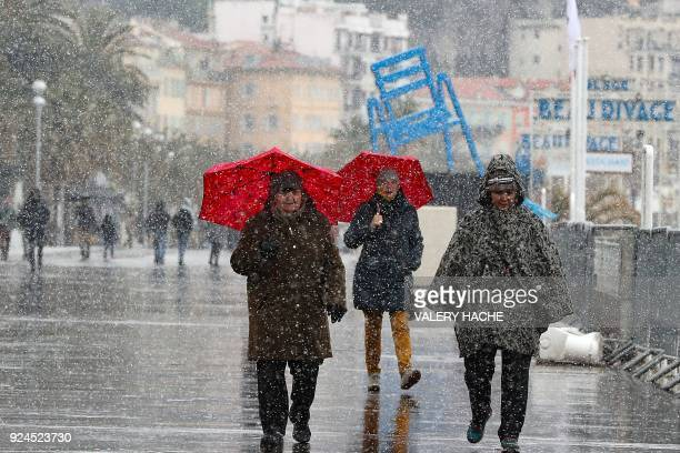 People walk through heavy snowfall on the Promenade des Anglais on February 26 2018 in Nice A wave of Siberian cold settled February 26 on the...